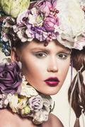 Fashion portrait of young attractive woman with flowers in her hair. Looking Stock Photos