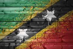 Painted saint kitts and nevis flag on a wooden texture Stock Photos