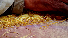 Indin craftsman sews / threads gold beads onto fabric, close up - stock footage