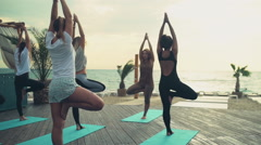 group of women practicing yoga on the beach slow motion - stock footage