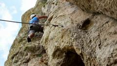 Hiker climbing on rock Stock Footage