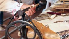 Woman using an antique winder for wrapping yarn onto a spool Stock Footage