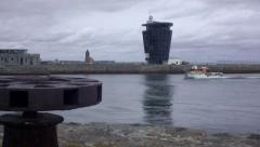 Small boat passes the control tower entrance at Aberdeen Harbour Stock Footage