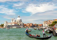 Transportation of tourists in gondolas. Main attraction in Venice. - stock photo
