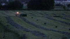 A farmer bailing hay at night Stock Footage