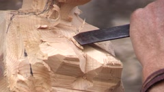 Stock Video Footage of Wood carver works with a chisel on the briest of a female statue - wood carving
