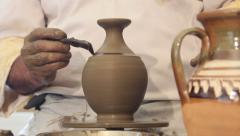 Craftsman shapes pottery on an classic potter's kick wheel - stock footage
