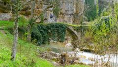 Crossover, crossing the ancient medieval stone arch bridge Stock Footage