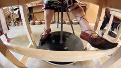 Woman working on a potter's kick wheel Stock Footage