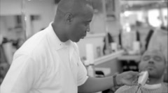 Barber gives man haircut and shaves beard shapeup barbershop black and white Stock Footage