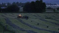 Farmer bailing hay at night Stock Footage