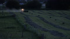 Farmer bailing hay in evening Stock Footage