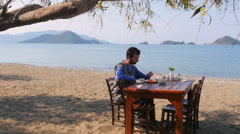 Tourist man eating, gorgeous breakfast beach with majestic sea background Stock Footage