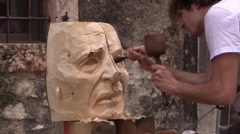 Wood carver with a chisel on right eye of sculpture - Public Carving Competition Stock Footage