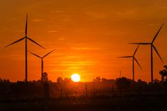 Eco power in wind turbine farm with sunset Kuvituskuvat