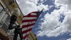 american flag flying in a historic old town - stock footage