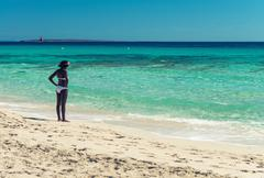 Afro american woman staring at ocean on a beautiful beach Stock Photos
