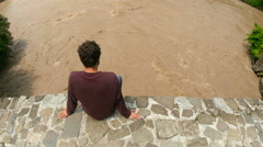Man sitting top historical arch bridge over river water stream Stock Footage
