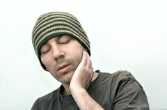 Man with swollen face suffering from toothache - stock photo