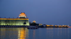 Chinese ancient gate tower surrounded by lake at night Stock Footage