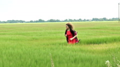 Slow motion. Pretty young woman running in field of wheat (clip 2). Stock Footage