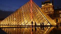 PARIS, FRANCE, Louvre museum and pyramide at dusk, people, tourists walking Stock Footage