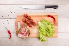 Tomato, toasts, meat and salad on wooden table Stock Photos