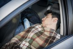 Young handosme man sleeping in his car Kuvituskuvat
