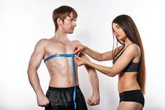 Girl measures volume of breast man Stock Photos