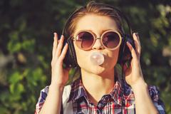 Hipster girl listening to music on headphones and chews the cud. Stock Photos