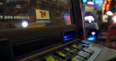 Woman feeds dollar bill into gambling machine Stock Footage