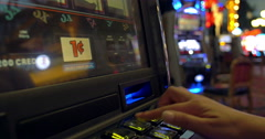 Woman gambles on betting machine in busy casino Stock Footage