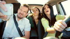 Three happy beautiful people in car making crazy funny faces for selfie Stock Footage