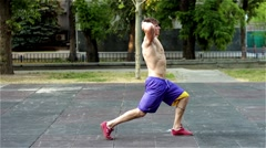 Handsome strong muscular guy working out at the park. Lunges. Stock Footage