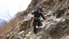 Woman walking on steep hike trail of Tiger Leaping Gorge Stock Footage