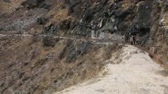 Woman walking on hike trail of Tiger Leaping Gorge Stock Footage