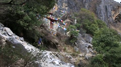 Hiking woman passing by traditional shrine at Tiger Leaping Gorge Stock Footage
