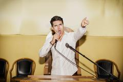 Passionate Man Speaking into Microphone in Meeting Stock Photos