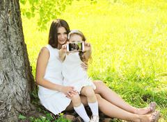 Mother and daughter child taking selfie portrait on the smartphone, sunny sum Stock Photos