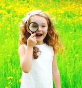 Portrait of positive little girl looking through a magnifying glass on summer - stock photo