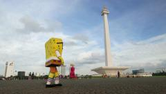 Beggar in SpongeBob SquarePants costume walk across Merdeka Square, Jakarta Stock Footage