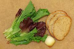 Fresh salad leaves and bread on wooden background. Stock Photos