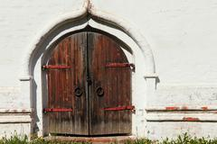 Old castle wooden gate and white wall. - stock photo