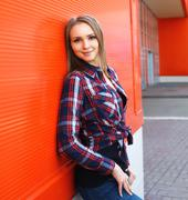 Portrait of beautiful smiling woman in checkered shirt against the red wall Stock Photos
