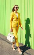 Fashion pretty young woman in yellow suit clothes with handbag walking agains Stock Photos