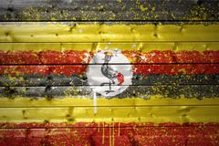 painted ugandan flag on a wooden texture - stock photo
