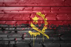painted angolan flag on a wooden texture - stock photo