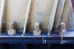 Big rusty metal nuts locked with rust and corrosion bolts - stock photo