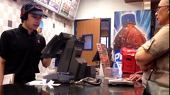 People ordering food at KFC check out counter Stock Footage