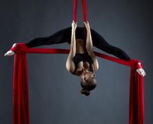 Sexy female acrobat performs hanging upside down - stock photo